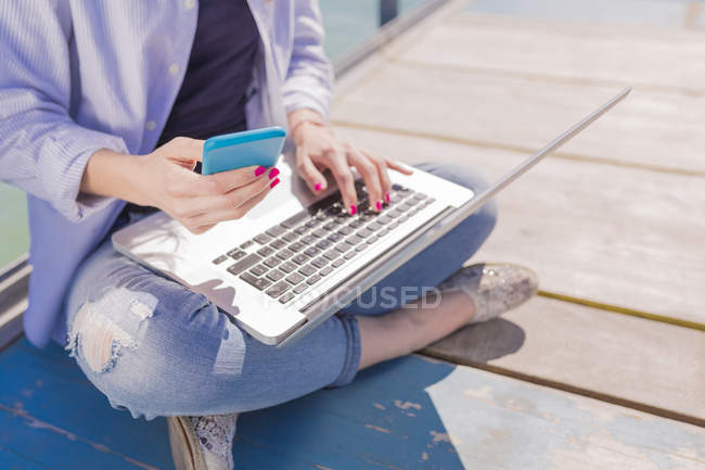 Young woman with laptop and smartphone, sitting on jetty — Stock Photo
