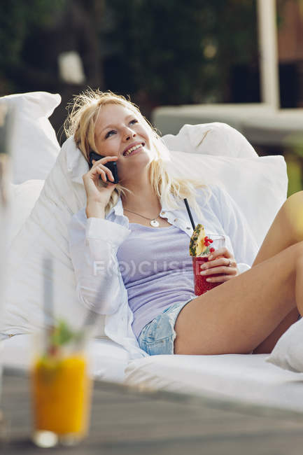 Portrait of telephoning young woman relaxing in an outdoor cafe — Stock Photo