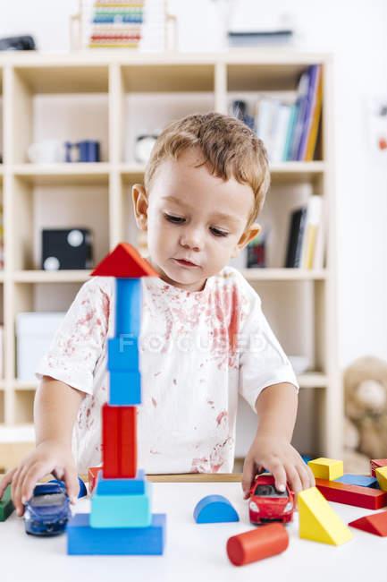 Kleiner Junge baut Turm mit blauen und roten Bausteinen — Stockfoto