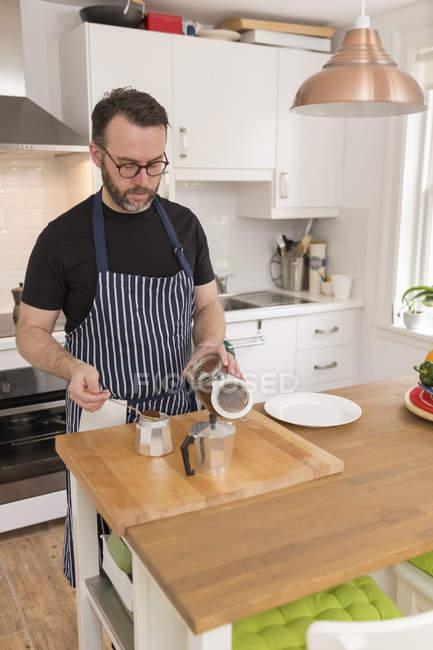 Чоловік готує еспресо на кухні — стокове фото