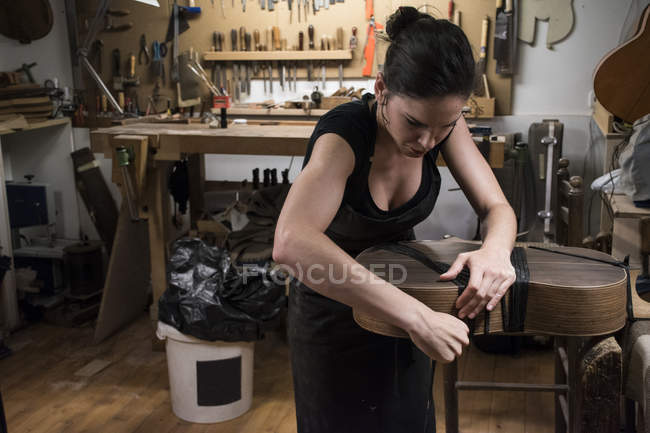 Luthier manufacturing a guitar in her workshop — Stock Photo