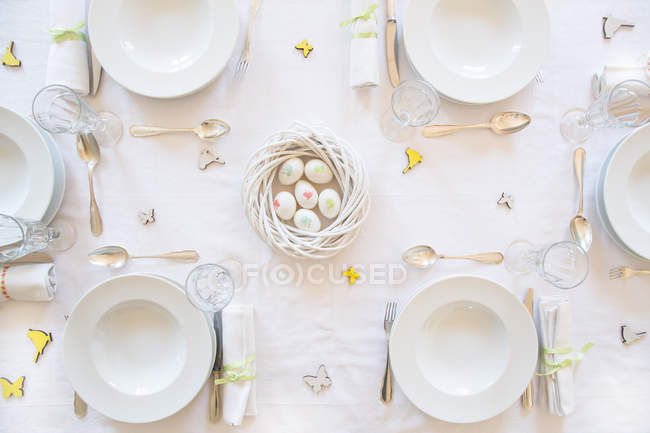 Laid Easter table decorated with nest of eggs — Stock Photo