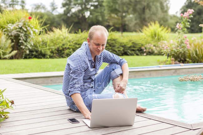 Uomo seduto al piano accanto a una piscina utilizzando il computer portatile — Foto stock