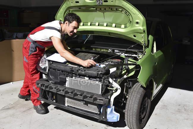Car mechanic examining accident damaged car before repair — Stock Photo
