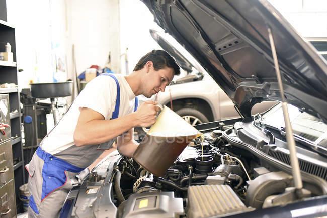 Car mechanic refilling engine oil — Stock Photo