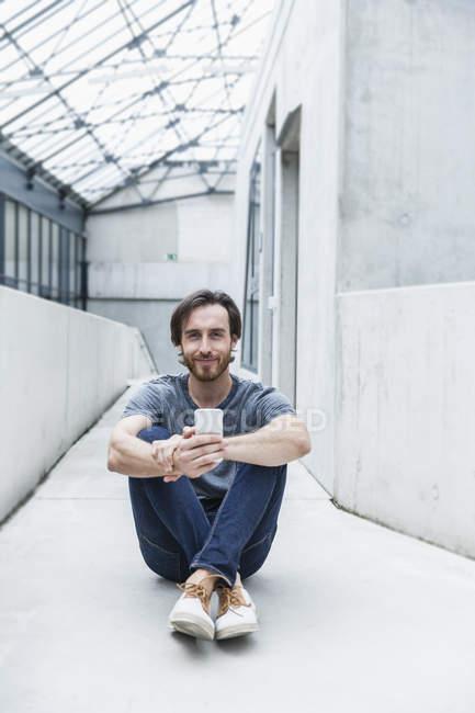 Retrato de um jovem sorridente sentado no chão com seu smartphone — Fotografia de Stock