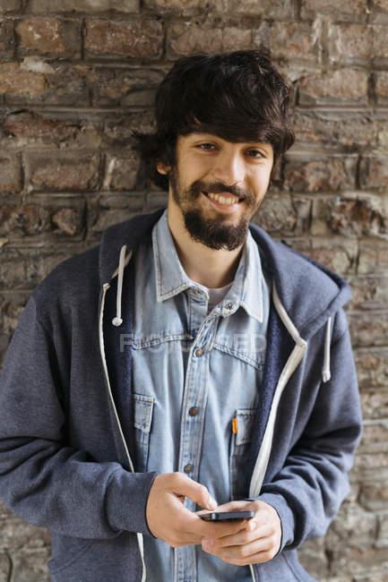 Портрет улыбающегося молодого человека со смартфоном — стоковое фото