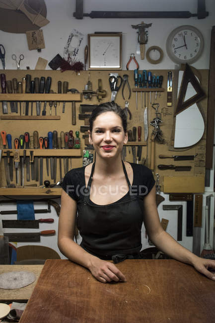 Portrait of smiling guitar maker standing in workshop — Stock Photo