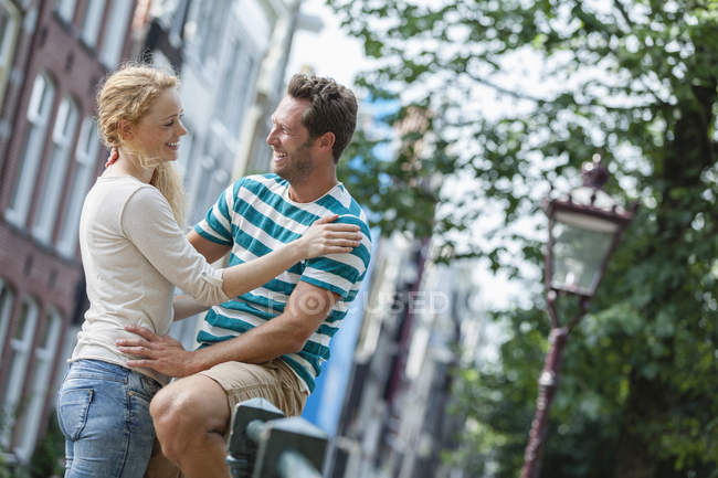 Pareja sonriente de Holanda, Amsterdam, abrazando al aire libre - foto de stock