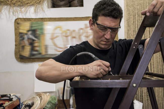 Человек в защитных очках чистит стул электрическим шлифовальным станком — стоковое фото