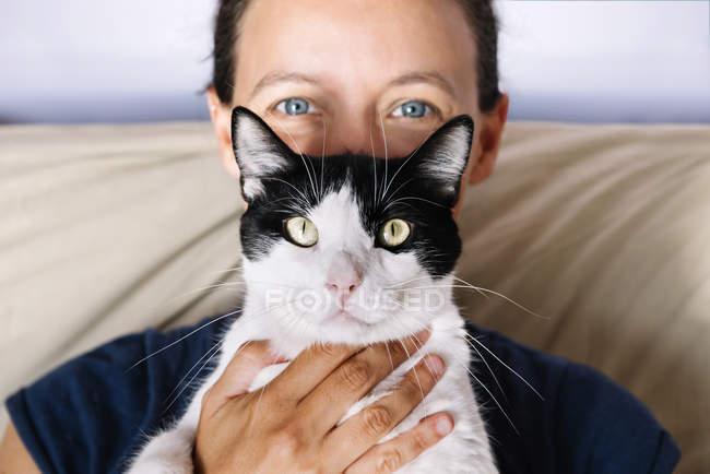 Голубоглазая женщина с черно-белой кошкой — стоковое фото