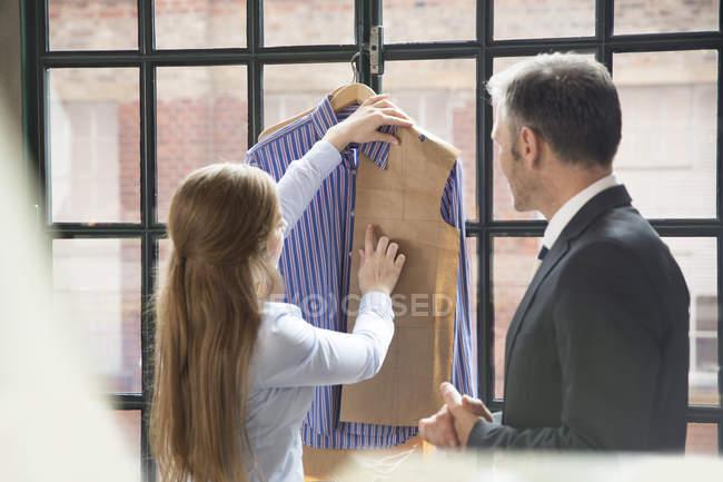 Young seamstress showing customer tailor made shirt — Stock Photo