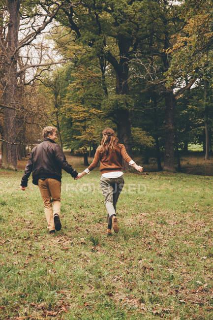 Пара бегущая в осеннем парке — стоковое фото