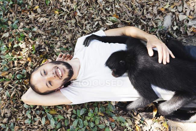 Bolivie, Coroico, homme souriant étendu sur le sol avec un singe araignée noir sur la poitrine — Photo de stock
