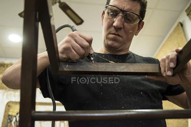 Homem com óculos de segurança limpando uma cadeira com uma lixadeira elétrica — Fotografia de Stock