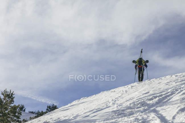 Spanien, Mann mit Skiern im Rucksack auf einem schneebedeckten Hügel, dem Penalara-Berg — Stockfoto
