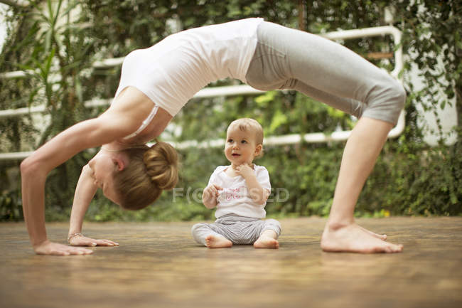 Woman doing yoga exercise while  baby watching her — Stock Photo