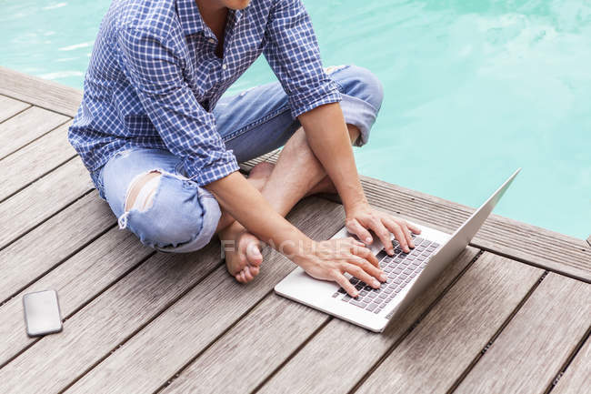 Man sitting on wooden floor beside a pool using laptop — Stock Photo