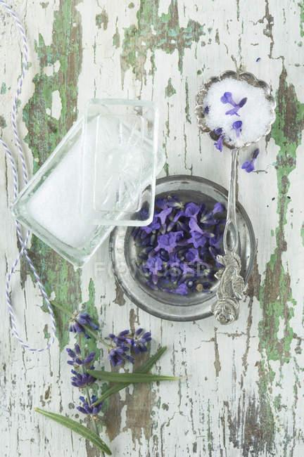 Fleurs de lavande et sucre dans un bol en verre, sur bois — Photo de stock