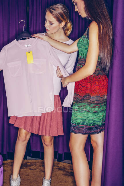 Two young women in fitting room with a blouse — Stock Photo
