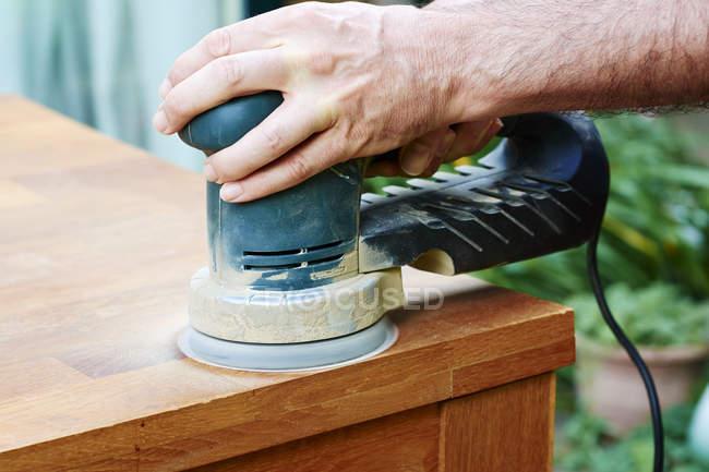 Человек шлифует дубовый стол случайным орбитальным шлифовальным станком крупным планом — стоковое фото