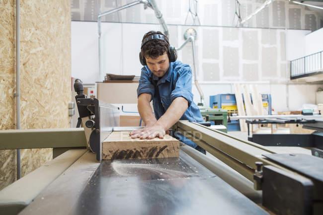 Плотник, работающий с пильным станком — стоковое фото