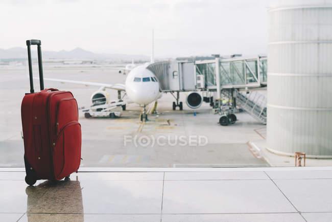 Valigia rossa in aeroporto con aeroplano sullo sfondo — Foto stock