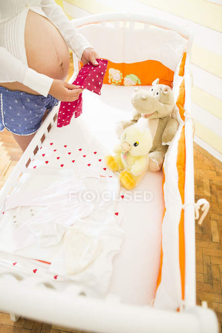 Pregnant woman besides a cot — Stock Photo