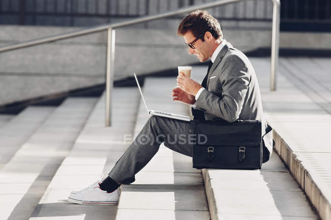 Businessman sitting on steps with cup of coffee — Stock Photo