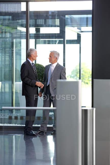 Два предпринимателя, говорить в офисе лобби — стоковое фото
