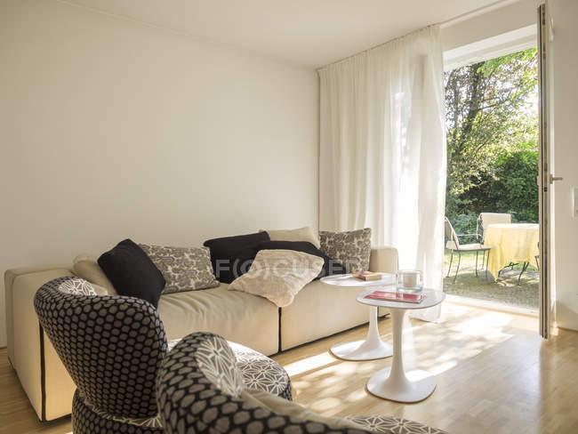 Современная гостиная в помещении и частичный вид на сад — стоковое фото