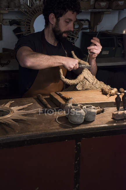 Ремесленник заплетает плетеную голову быка в своей мастерской — стоковое фото