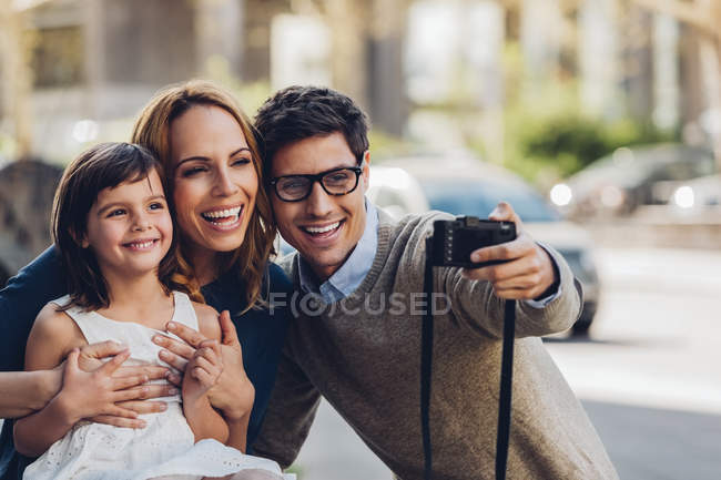 Man outdoors taking a selfie of his family with digital camera — Stock Photo