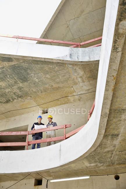 Строитель и архитектор с планом беседуют на строительной площадке — стоковое фото