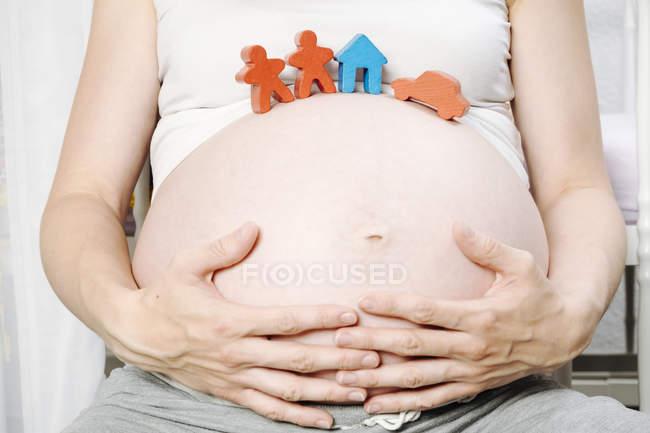 Беременная женщина перед детской кроваткой с игрушечным домиком, игрушечными фигурками и игрушечной машиной на животе — стоковое фото