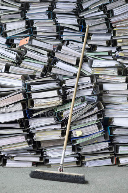 Piles of office folders and files with broom — Stock Photo