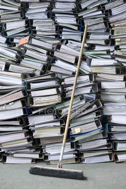 Montones de carpetas de oficina y archivos con escoba - foto de stock
