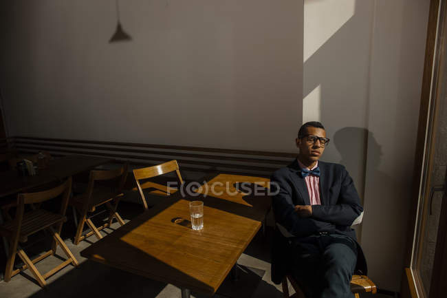 Young man sitting in cafe, waiting for someone, eyes closed — Stock Photo