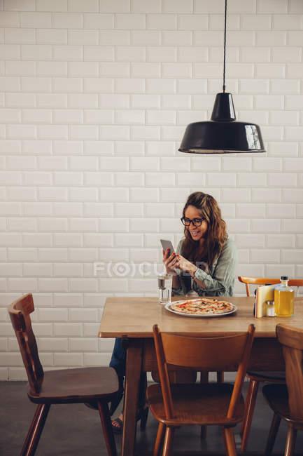 Jovem mulher comendo pizza no restaurante, usando telefone celular — Fotografia de Stock