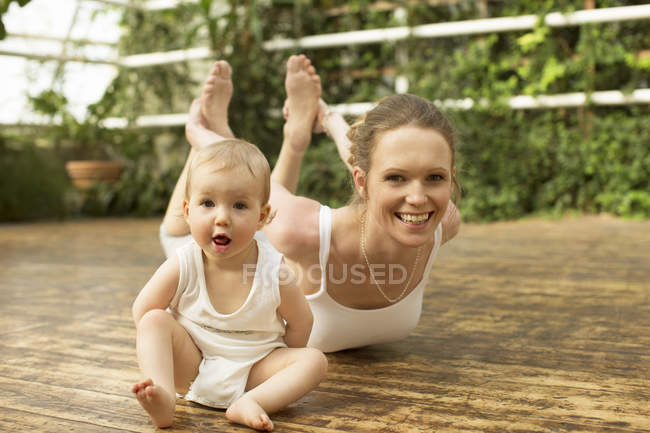 Portrait of baby sitting in front of mother doing yoga exercise — Stock Photo
