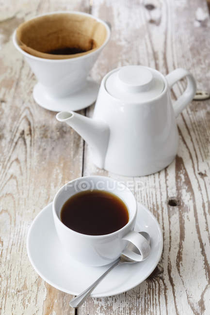 Cup of black filtered coffee and coffee pot on wood — Stock Photo