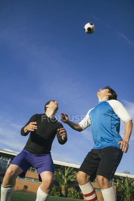 Два футболісти близько, щоб головою м'яч — стокове фото