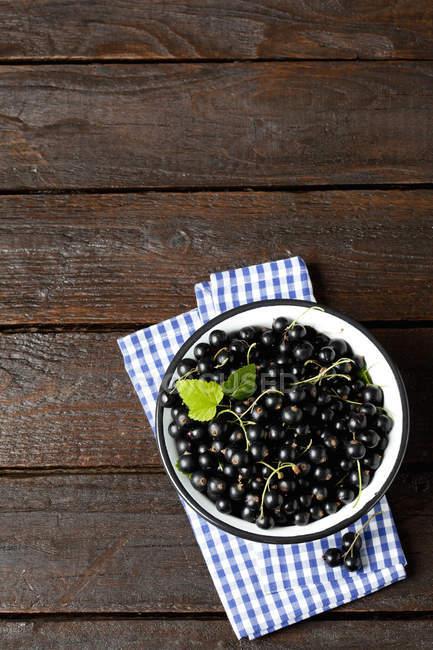 Schale mit schwarzen Johannisbeeren auf Tuch — Stockfoto