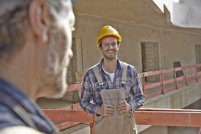 Smiling man with hard hat on construction site — Stock Photo