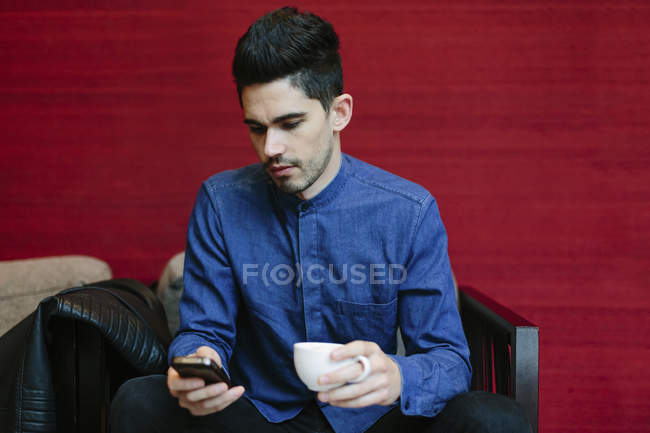 Young man with coffee cup looking at his smartphone — Stock Photo