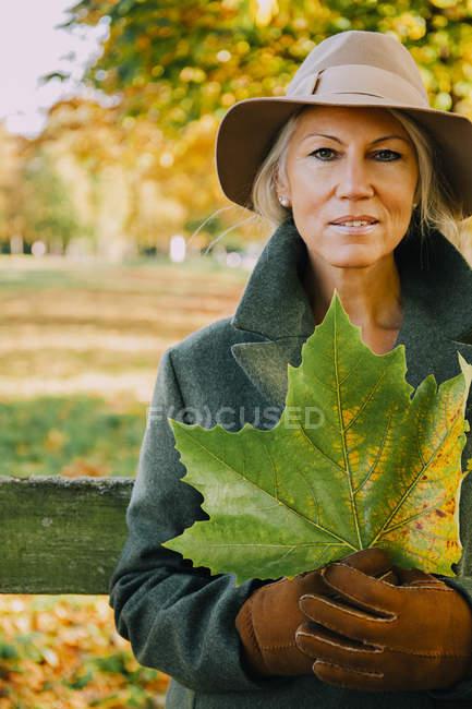 Портрет жінка носить капелюх проведення Осіннє листя у парку — стокове фото