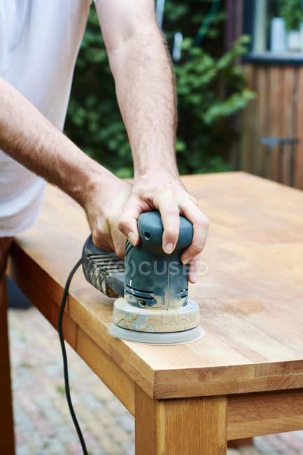 Человек шлифует дубовый стол со случайным орбитальным песком — стоковое фото