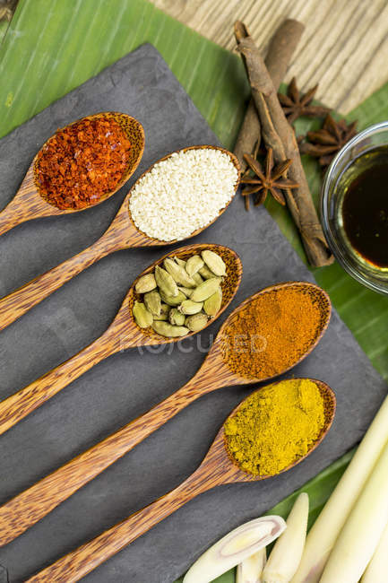 Different spices in wooden spoons on table — Stock Photo