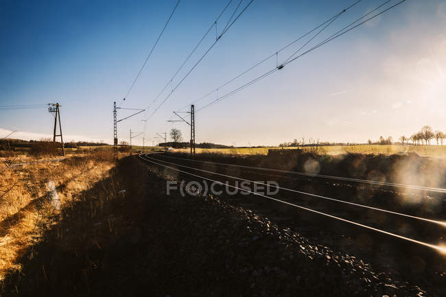 Germany, Burgstemmen, rails and power lines at rural scene — Stock Photo