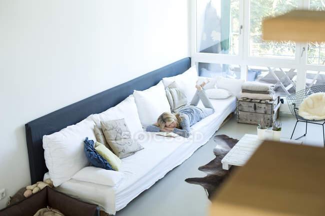 Mujer relajándose en el sofá en su sala de estar - foto de stock